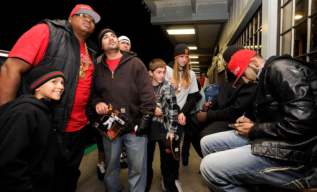 . Nearly 3-1/2 hours into their appearance, Rapper E-40, left, and Giants reliever Sergio Romo, move outdoors to greet their line of fans at Kinder\'s Meat and Deli on Wednesday, Dec. 12,  2012, in Pleasant Hill, Calif. (Susan Tripp Pollard/Staff)