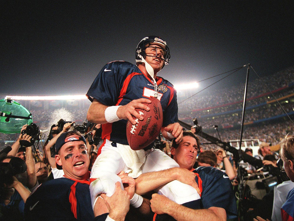 Description of . Denver Broncos quarterback John Elway (C) is carried by teammates Ed McCaffrey (L) and Bubby Brister (R) after the Broncos defeated the  Green Bay Packers 31-24 to win Super Bowl XXXII in San Diego, CA 25 January. TIMOTHY A. CLARY/AFP/Getty Images