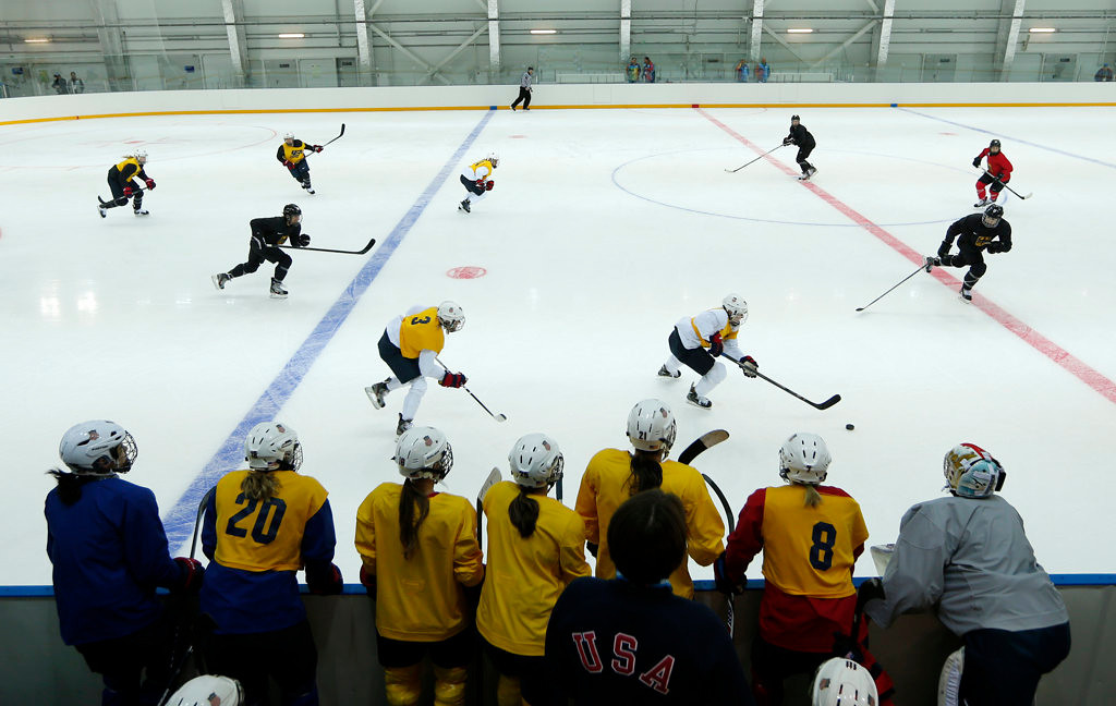 . Players of the U.S. women\'s ice hockey team watch from a bench as their teammates scrimmage against Germany during their practice session ahead of the 2014 Winter Olympics, Tuesday, Feb. 4, 2014, in Sochi, Russia. (Associated Press: Petr David Josek)