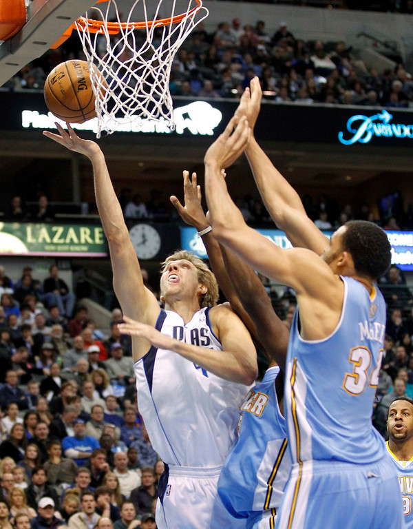 . Dallas Mavericks forward Dirk Nowitzki (L) shoots against Denver Nuggets forward Kenneth Faried and center JaVale McGee (R) during the first half of their NBA basketball game in Dallas, Texas, December 28, 2012. REUTERS/Mike Stone (UNITED STATES - Tags: SPORT BASKETBALL)