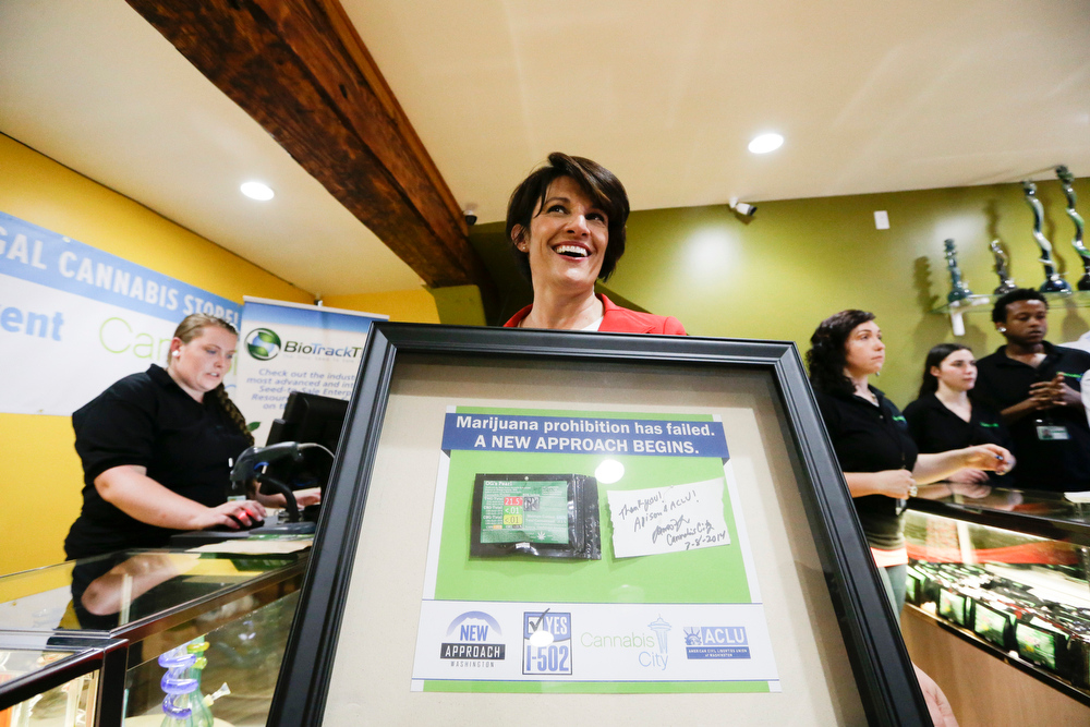 . Alison Holcomb, criminal justice director at the Washington state ACLU, poses with a plaque containing the marijuana she purchased at the Cannabis City retail marijuana store on July 8, 2014 in Seattle, Washington. Cannabis City was the first retail marijuana store to open in Seattle today and one of the first group now operating in Washington state, nearly a year and a half after the state\'s voters chose to legalize marijuana for recreational use.  (Pool photo by Elaine Thompson/AP)
