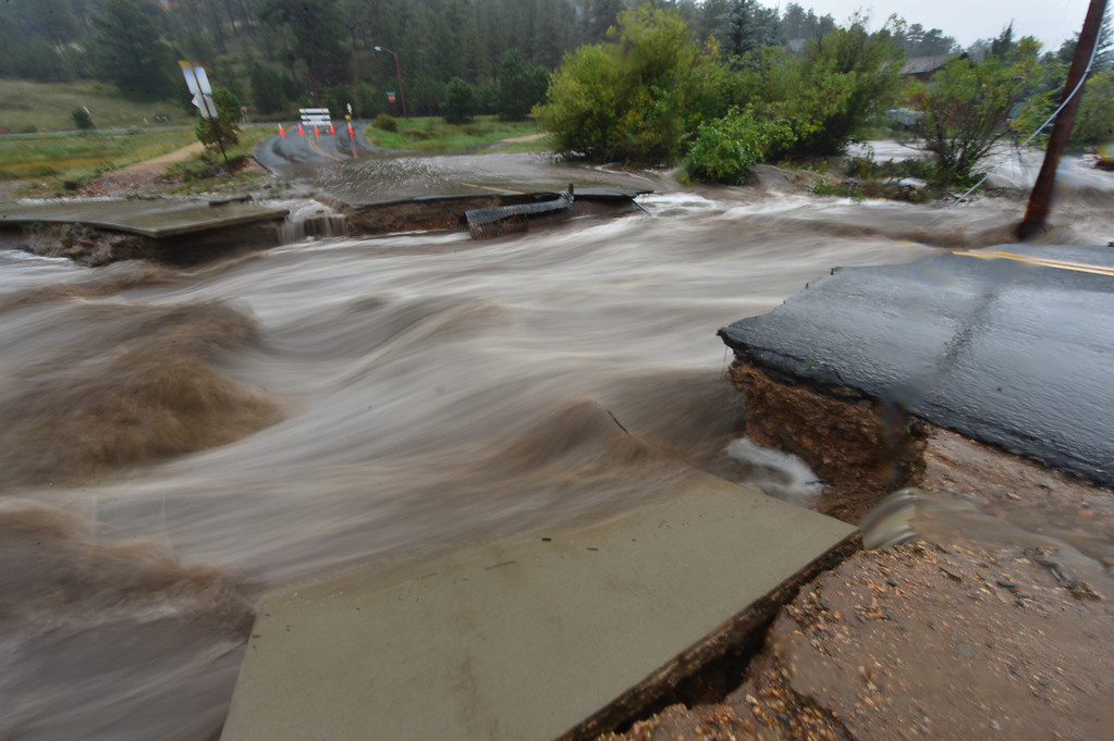. Fish Creek rushes past Scott Avenue, taking part of the street down stream on Thursday, Sept 12, 2013. The East side of Fish Creek was isolated by the flood, as the normally small creek washed away streets and bridges. Walt Hester/Estes Park Trail-Gazette