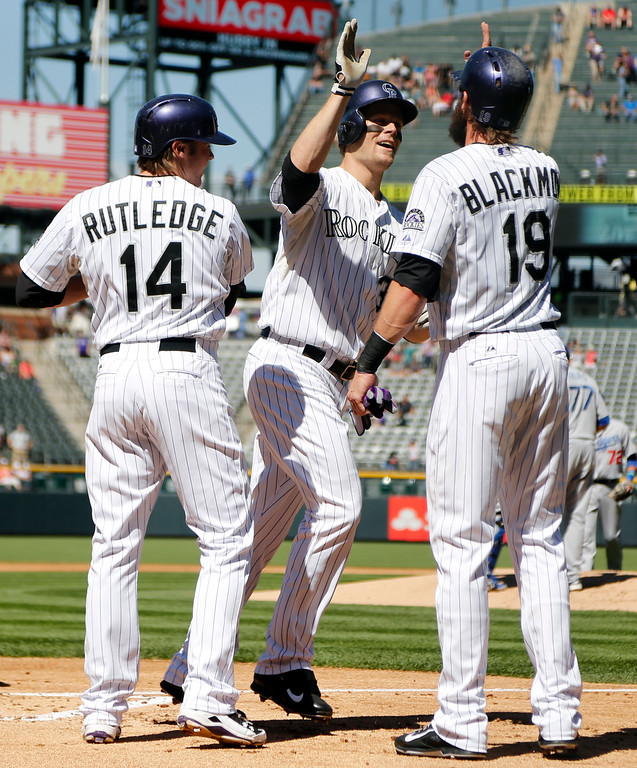 . Colorado Rockies\' Justin Morneau (33) is congratulated at the plate by Josh Rutledge (14), and Charlie Blackmon (19) after hitting a three-run home run off Los Angeles Dodgers starting pitcher Carlos Frias during the first inning of a baseball game Wednesday, Sept. 17, 2014, in Denver. (AP Photo/Jack Dempsey)