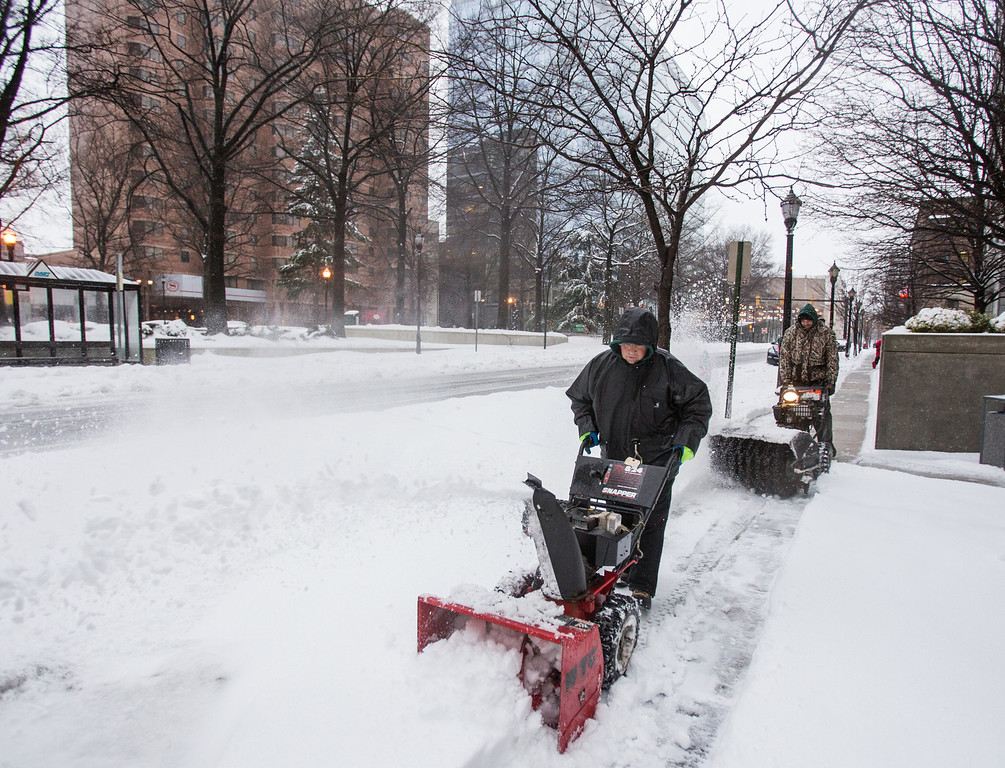 . Randy Harbaugh, left, and Craig Lester, right, work to clear the sidewalk along 11th street, in downtown Wilmington, Del. on Thursday morning, Feb. 13, 2014. The city saw nearly a foot of snow fall over night, and residents were forced to dig out in blowing sleet in the morning. (AP Photo/The News Journal, Kyle Grantham)