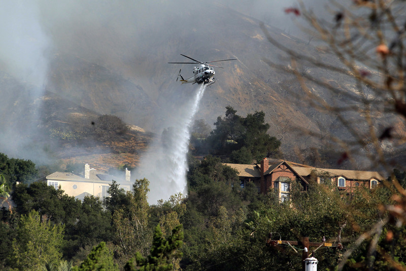 . A firefighting helicopter makes a water drop over homes in Glendora, Calif. as a wildfire burns in the hills just north of the San Gabriel Valley community on Thursday, Jan 16, 2014. Southern California authorities have ordered the evacuation of homes at the edge of a fast-moving wildfire burning in the dangerously dry foothills of the San Gabriel Mountains. (AP Photo/Ringo H.W. Chiu)