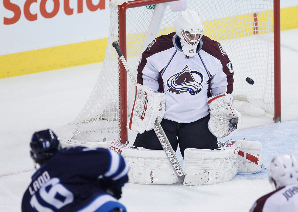 . Winnipeg Jets\' Andrew Ladd (16) scores on Colorado Avalanche goaltender Reto Berra during the first period of an NHL hockey game Wednesday, March 19, 2014, in Winnipeg, Manitoba. (AP Photo/The Canadian Press, John Woods)