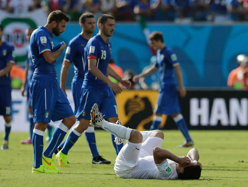 . Uruguay\'s Luis Suarez lies on the ground as Italian players leave the pitch after their 1-0 loss to Uruguay during the group D World Cup soccer match at the Arena das Dunas in Natal, Brazil, Tuesday, June 24, 2014. (AP Photo/Petr David Josek)
