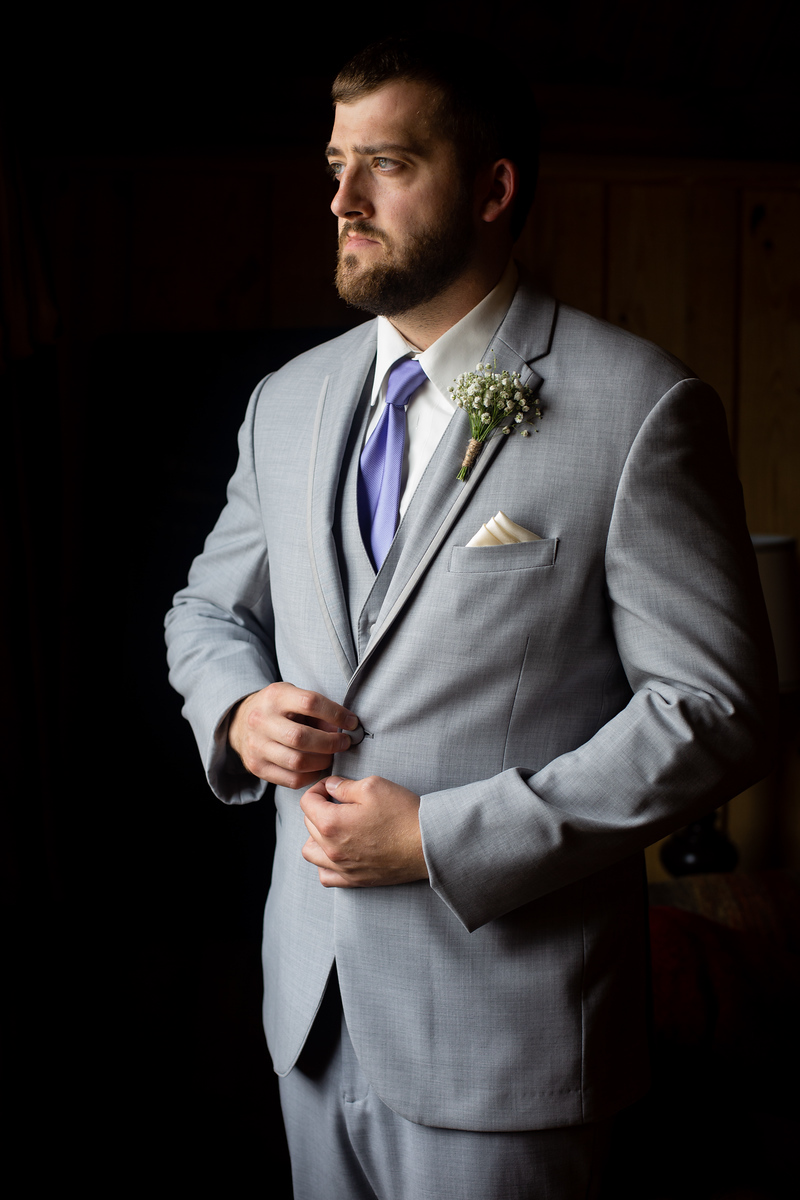 groom standing near a window wearing a grey three piece suit with a purple