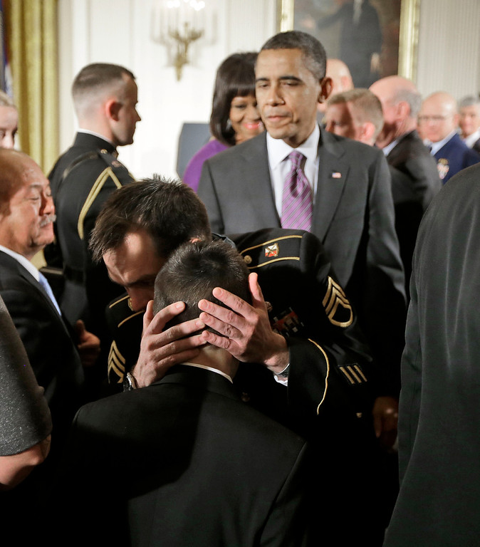 . President Barack Obama watches as Medal of Honor recipient retired Staff Sgt. Clinton Romesha, facing camera, hugs MacAidan Gallegos, son of the late Sgt. Justin Gallegos, following Romesha\'s medal of honor ceremony in the East Room of the White House in Washington, Monday, Feb. 11, 2013. Sgt. Gallegos was one of eight who died as Romeshan fought back an intense daylong barrage by enemy fighters as the Taliban descended on Combat Outpost Keating in the mountains near the Pakistan border on Oct. 3, 2009.(AP Photo/Pablo Martinez Monsivais)