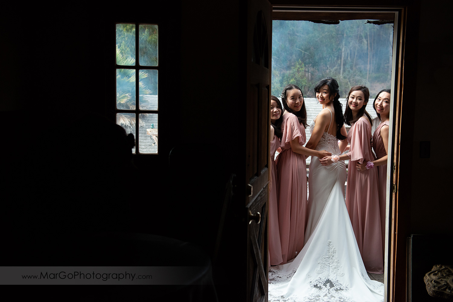 bride in white dress and bridesmaids in pink dresses looking back thorugh the door at Long Branch Saloon & Farms in Half Moon Bay