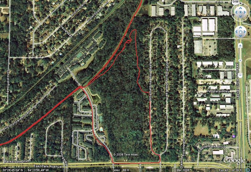 """Google Earth jpeg of the area. That's Park Avenue running east-west along the bottom, Capital Circle NE/US319 running north-south along the right edge. The narrow tall oval neighborhood is Breckenridge on Park, aka Whetherbine Way. Access the Bog section from the Whetherbine """"dog walk"""" or from Fern Trail (lower left to top center). Polos on Park apartments are to the left of this boggy greenspace. The log rides are up near (and to the left/southwest of) the """"point"""" of the red GPS track, top center."""