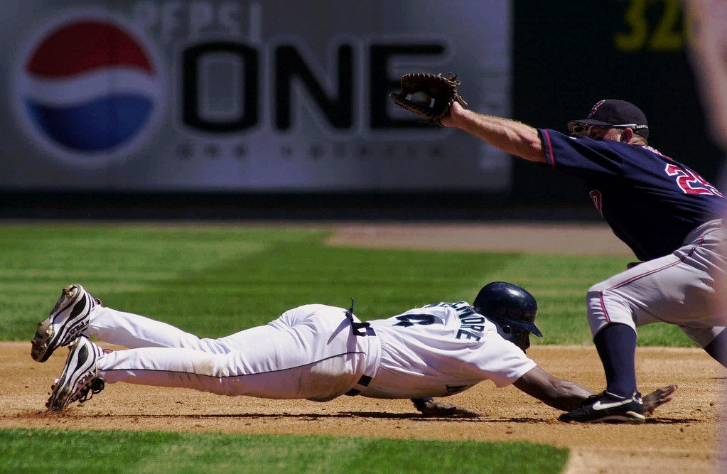 . Seattle Mariners\' Mark McLemore, left, dives back to the bag as Cleveland Indians first baseman Jim Thome takes the attempted pickoff throw from pitcher Bartolo Colon during the first inning Saturday, Aug. 12, 2000, in Seattle. McLemore went on to score on a double by Alex Rodriguez. (AP Photo/Jay Drowns)