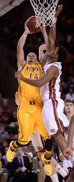 . Denver Pioneers guard Cam Griffin (30) blocks a shot by Wyoming Cowboys guard Josh Adams (14) during the first half December 15, 2013 Magness Arena. (Photo by John Leyba/The Denver Post)