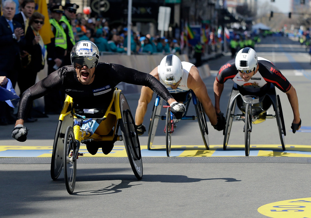 . Marcel Hug, of Switzerland, left, celebrates after winning ahead of Kurt Fearnley, of Australia, center, and Ernst Van Dyk, of South Africa, in the wheelchair division of the 120th Boston Marathon on Monday, April 18, 2016, in Boston. (AP Photo/Elise Amendola)