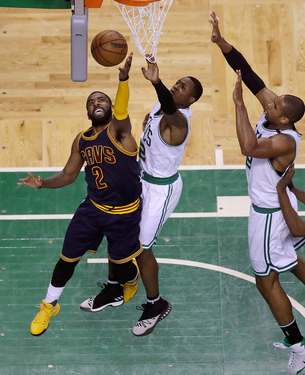 . Cleveland Cavaliers guard Kyrie Irving (2) shoots against Boston Celtics guard Terry Rozier, center, and center Al Horford during the second quarter of Game 1 of the NBA basketball Eastern Conference finals, Wednesday, May 17, 2017, in Boston. (AP Photo/Charles Krupa)