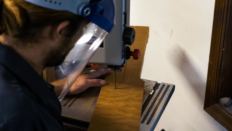 Blake Burns uses a band saw to cut out the basic shape of a guitar neck in the Lust for Tone guitar shop in Lake Worth on Monday, July 16, 2018. (Joseph Forzano / The Palm Beach Post)