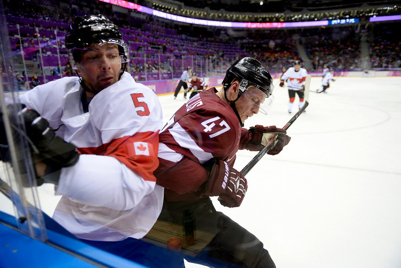 . Martins Cipulis (47) of the Latvia and Dan Hamhuis (5) of the Canada battle on the glass during the second period of men\'s hockey action. Sochi 2014 Winter Olympics on Wednesday, February 19, 2014 at Bolshoy Ice Arena. (Photo by AAron Ontiveroz/ The Denver Post)