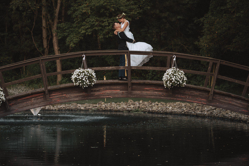 A groom lifts his bride up on a bridge and looks deeply into her eyes.