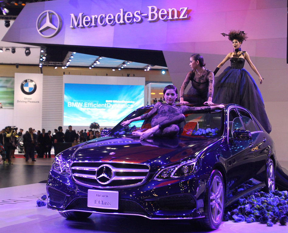 . Thai models pose on a Mercedes-Benz E-class sedan on the press day of the Bangkok Motor Show in Bangkok, Thailand, Tuesday, March 26, 2013. The 34th running of the show is opened to the public from Wednesday. (AP Photo/Sakchai Lalit)