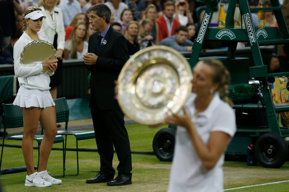 Description of . Petra Kvitova of Czech Republic, right, kisses the trophy after winning the women's singles final against Eugenie Bouchard of Canada, left, at the All England Lawn Tennis Championships in Wimbledon, London, Saturday July 5, 2014. (AP Photo/Pavel Golovkin)