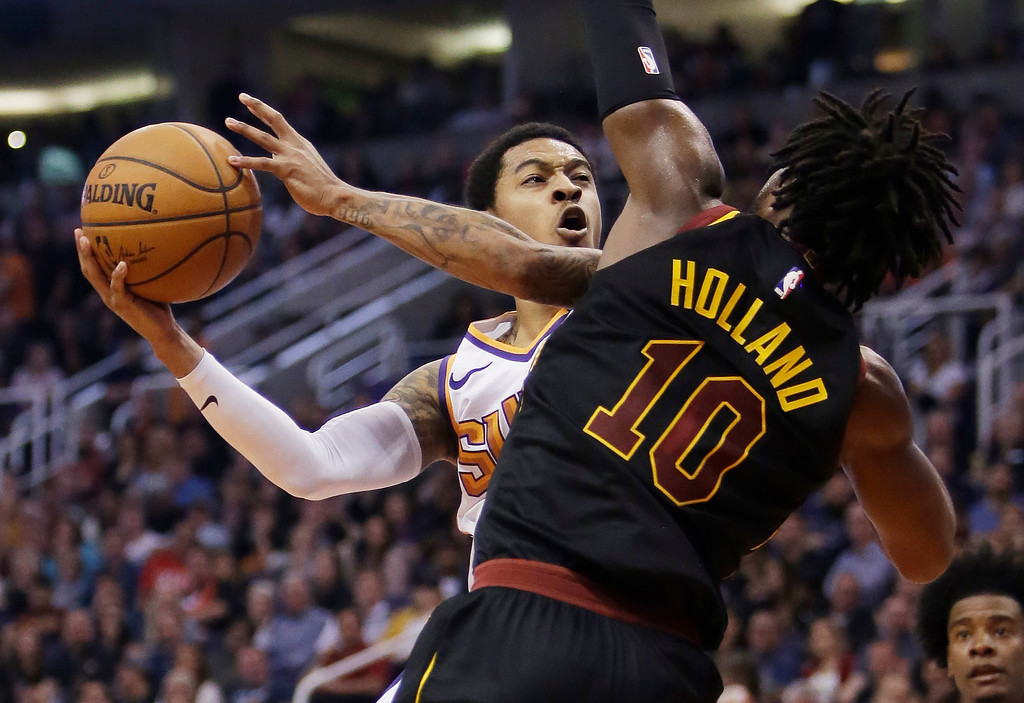 . Phoenix Suns guard Tyler Ulis (8) drives on Cleveland Cavaliers guard John Holland in the second half during an NBA basketball game, Tuesday, March 13, 2018, in Phoenix. The Cavaliers defeated the Suns 129-107. (AP Photo/Rick Scuteri)