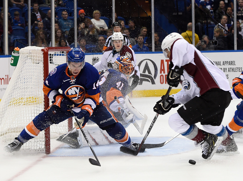 . New York Islanders goalie Jaroslav Halak (41) keeps his eyes on the puck as  Islanders defenseman Thomas Hickey (14) defends against Colorado Avalanche right wing Jarome Iginla (12) in the third period of an NHL hockey game at Nassau Coliseum on Tuesday, Nov. 11, 2014, in Uniondale, N.Y. The Islanders won 6-0. (AP Photo/Kathy Kmonicek)