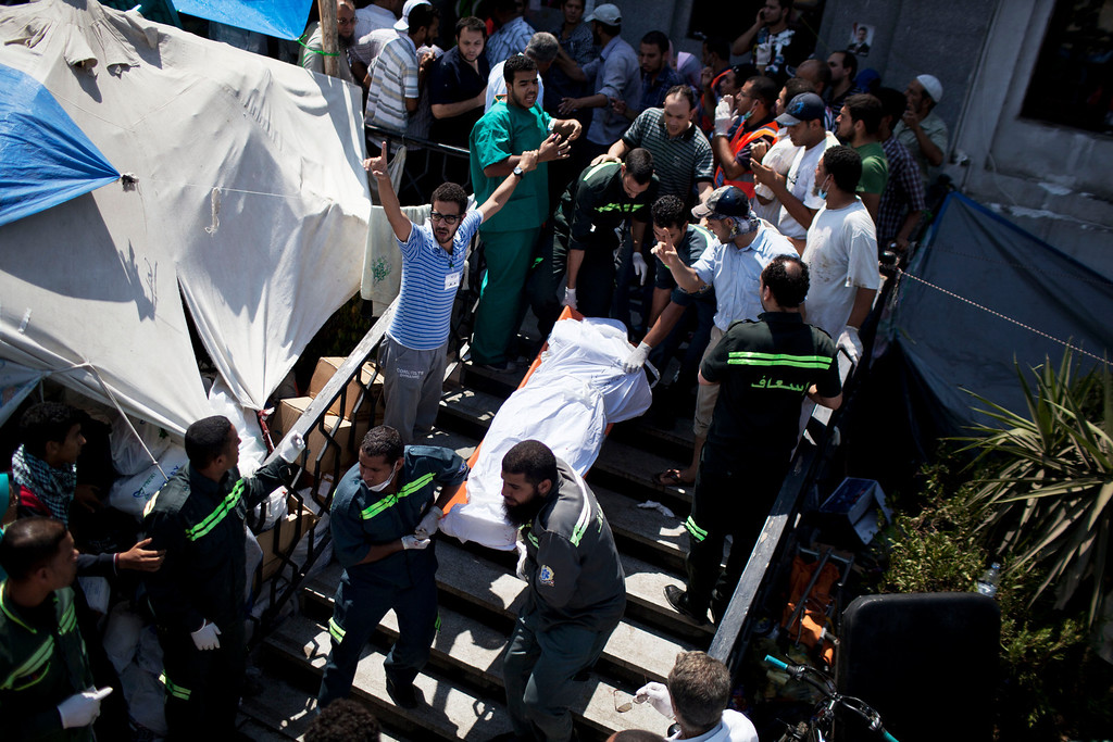 . Doctors move the corpse of a supporter of Egypt\'s ousted President Mohammed Morsi killed during clashes with security forces at Nasr City, where pro-Morsi protesters have held a weeks-long sit-in, in a field hospital in Cairo, Egypt, Saturday, July 27, 2013.  Overnight clashes between security forces and supporters of ousted Egyptian President Mohammed Morsi in east Cairo left scores of protesters dead and hundreds injured following a day of massive pro-military rallies backing a tough hand against Morsiís backers and the Muslim Brotherhood group from which he hails. (AP Photo/Manu Brabo)