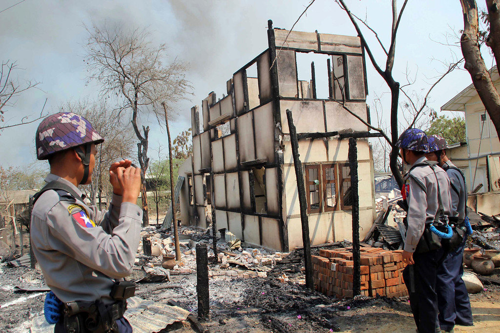 . In this Thursday, March. 21, 2013, police officers stand near burnt building in Meikhtila, where Ethnic unrest between Buddhists and Muslims continues, in Mandalay division, about 550 kilometers (340 miles) north of Yangon, Myanmar, Friday, March.22, 2013. (AP Photo)