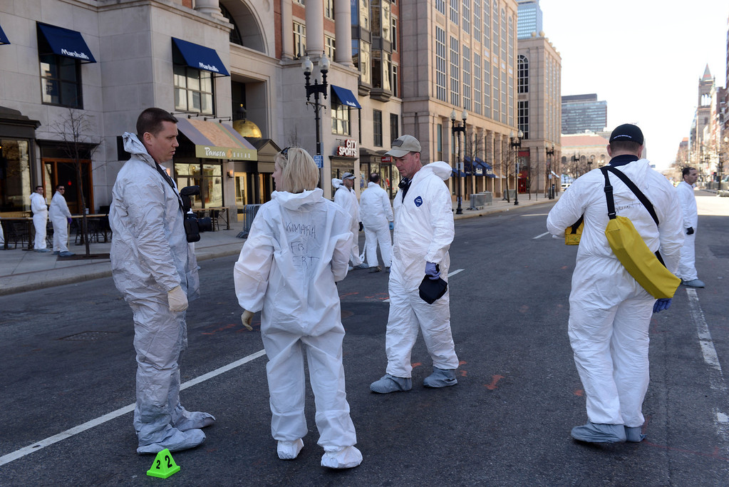 . FBI crime scene investigators stand near an evidence marker on Boylston Street just past Berkeley Street near the scene of the Boston Marathon bombing April 17, 2013 in Boston, Massachusetts. Investigators continue to work the scene of two bomb explosions at the finish line of the marathon that killed 3 people and injured over one hundred more. (Photo by Darren McCollester/Getty Images)