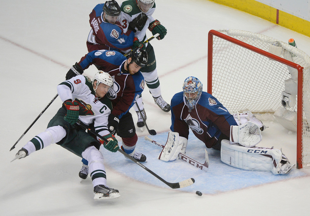 . Colorado center Ryan O\'Reilly (90) pushed Minnesota center Mikko Koivu (9) off the puck in front of goalie Semyon Varlamov in the third period. The Colorado Avalanche defeated the Minnesota Wild 4-2 at the Pepsi Center Saturday night, April 19, 2014 in an NHL playoff game. (Photo by Karl Gehring/The Denver Post)