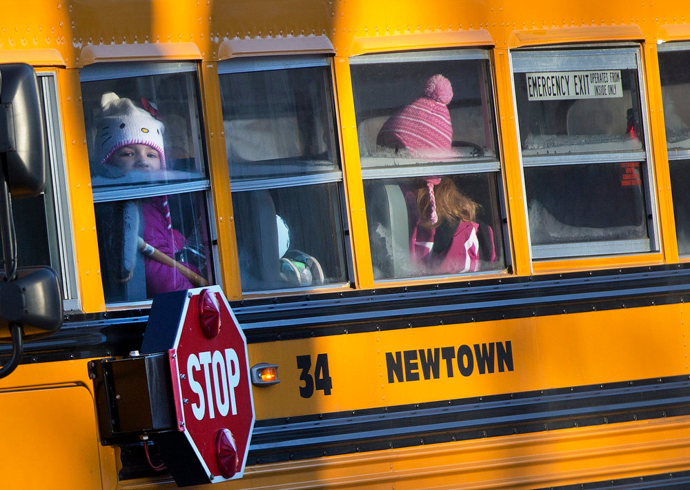 Description of . Children from Sandy Hook Elementary School are seen on a school bus making their way to their new school in Monroe as they leave Newtown, Connecticut January 3, 2013. Hundreds of the children who escaped the harrowing attack on their elementary school in Newtown, Connecticut, last month head back to classes on Thursday for the first time since a gunman killed 20 of their schoolmates and six staff members. School officials are preparing for droves of anxious parents to join the fleet of buses carting children to a disused middle school in the neighboring town of Monroe. REUTERS/Shannon Stapleton
