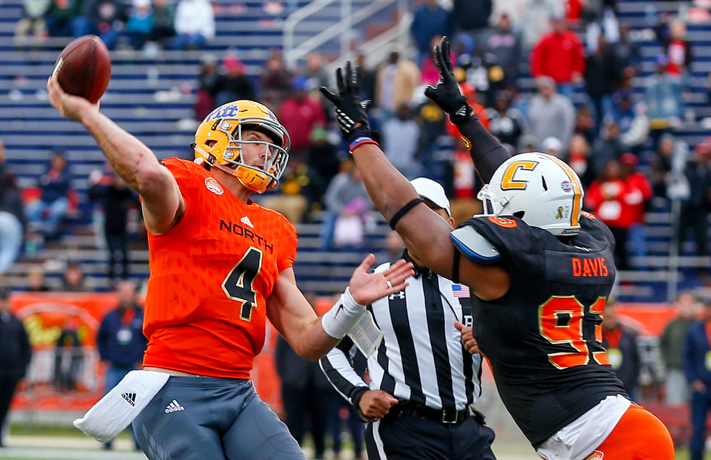 . North squad quarterback Nate Peterman of Pittsburgh (4) throws a pass as South squad defensive end Keionta Davis of UT-Chattanooga (93) puts pressure during the second half of the Senior Bowl NCAA college football game, Saturday, Jan. 28, 2017, at Ladd-Peebles Stadium in Mobile, Ala. (AP Photo/Butch Dill)