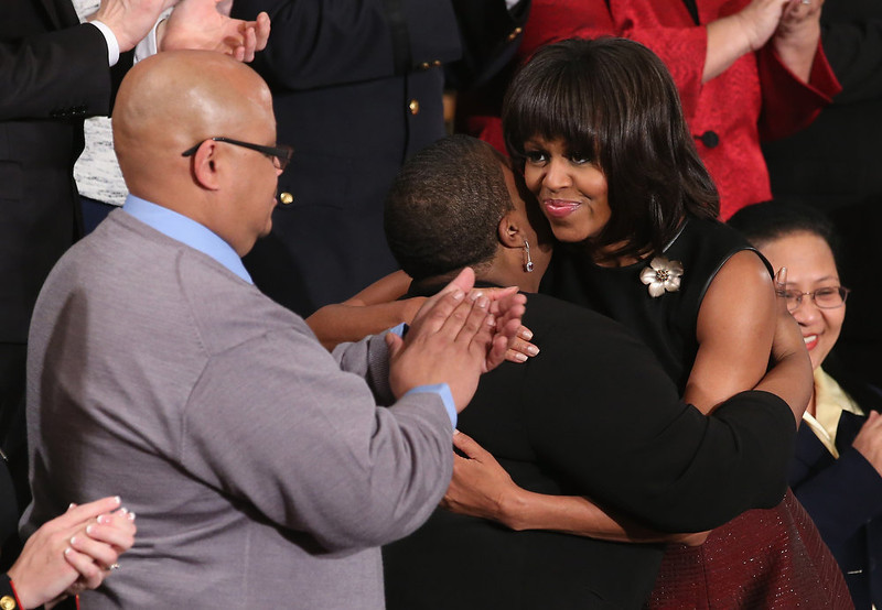 . U.S. first lady Michelle Obama (R) hugs Cleopatra Cowley-Pendleton (C) and Nathaniel A. Pendleton Sr. (L) of Chicago, Illinois before U.S. President Barack Obama\'s State of the Union speech at the U.S. Capitol February 13, 2013 in Washington, DC. The Pendleton\'s daughter, Hadiya Pendleton, was murdered on January 29, 2013, when she was shot and killed in Harsh Park on Chicago�s South Side.  (Photo by Chip Somodevilla/Getty Images)