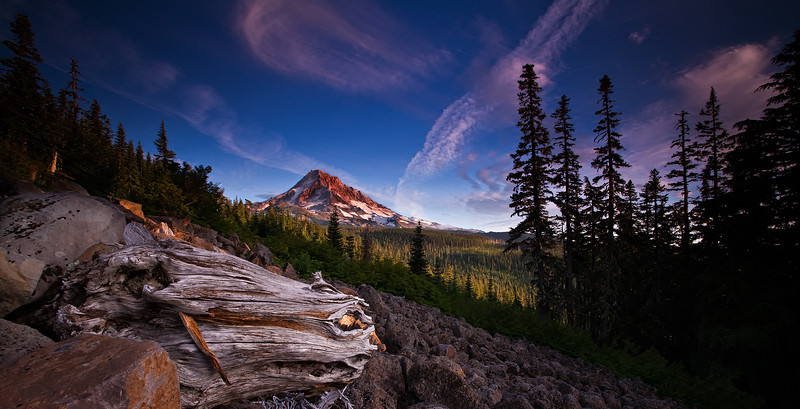 Mt Hood one of Oregons most recognized land marks in late August as the sun begins to set. Even without a blanket of snow the mountain is so beautiful as it is illuminated by the alpenglow of the setting summer sun.