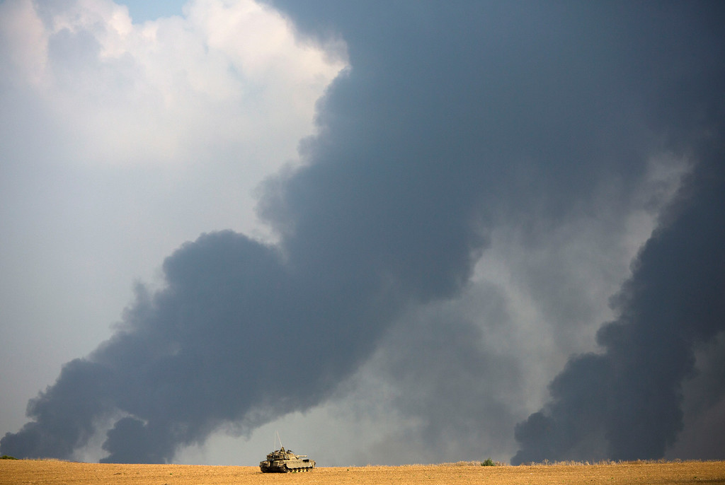 . An Israeli tank sits in a field as heavy smoke rises from the Gaza Strip Tuesday, July 22, 2014. Israeli airstrikes pummeled a wide range of targets in the Gaza Strip on Tuesday as the U.N. chief and the U.S. secretary of state began an intensive effort to end more than two weeks of fighting that has killed hundreds of Palestinians and tens of Israelis. (AP Photo/Dusan Vranic)