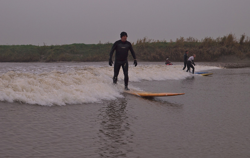 Steve with other surfers riding the Severn bore.