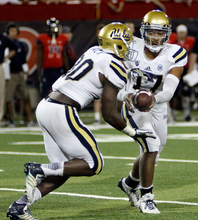 . UCLA\'s starting quarterback Brett Hundley (17) hands off the ball to Myles Jack (30) in the second half of an NCAA college football game against Arizona, Saturday, Nov. 9, 2013 in Tucson, Ariz.  UCLA won 31 - 26. (AP Photo/Wily Low)