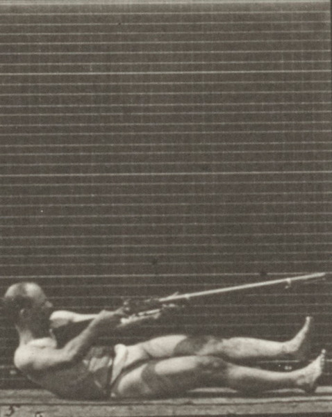 Man in pelvis cloth lying on back and firing bayonet