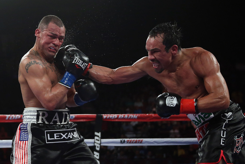 . INGLEWOOD, CA - MAY 17:  Juan Manuel Marquez (R) lands a right hand to the chin of Mike Alvarado at The Forum on May 17, 2014 in Inglewood, California.  (Photo by Jeff Gross/Getty Images)