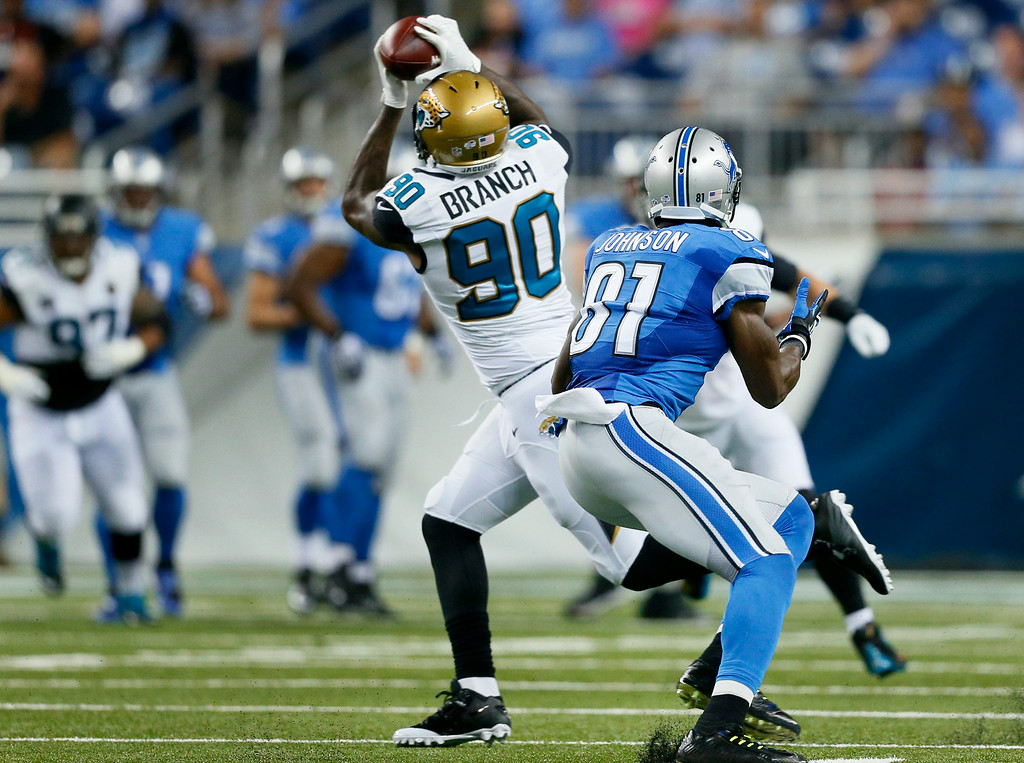 . Jacksonville Jaguars defensive end Andre Branch (90) intercepts a pass as Detroit Lions wide receiver Calvin Johnson (81) looks on in the first half of a preseason NFL football game at Ford Field in Detroit, Friday, Aug. 22, 2014. (AP Photo/Rick Osentoski)