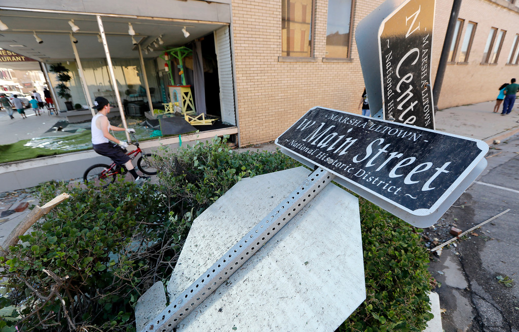 . A local resident rides his bike past a toppled street sign on Main Street, Thursday, July 19, 2018, in Marshalltown, Iowa. Several buildings were damaged by a tornado in the main business district in town including the historic courthouse. (AP Photo/Charlie Neibergall)