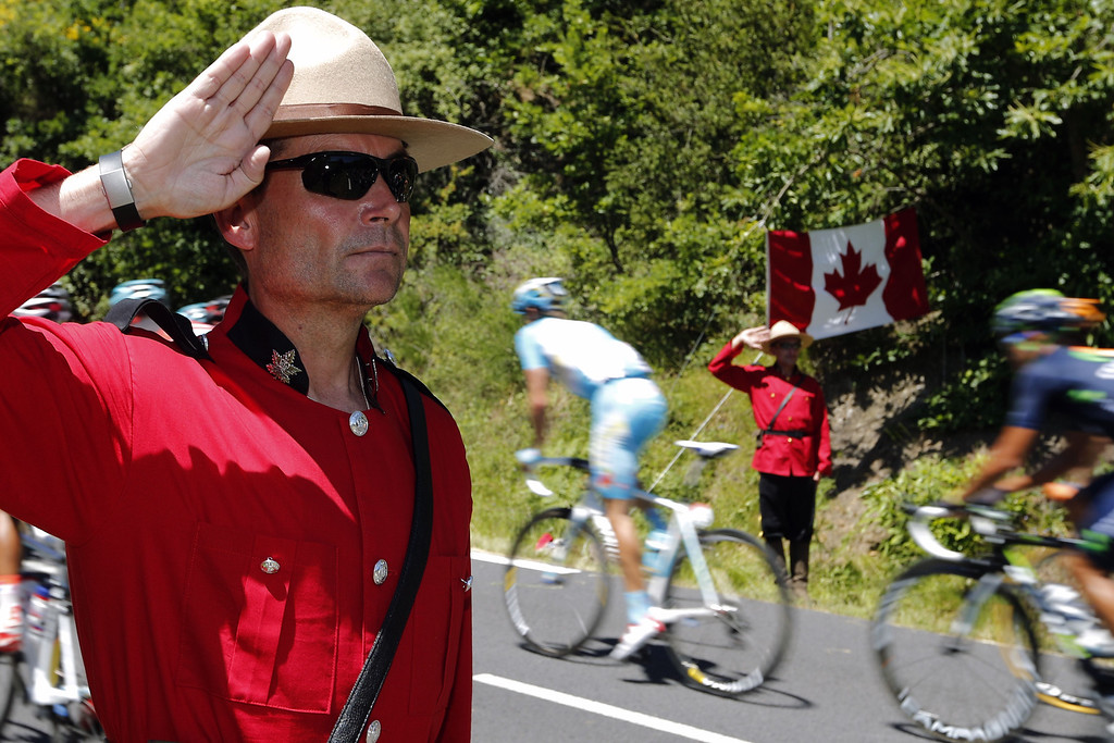 . Supporters dressed like Canadian mounted policemen make the military salute as cyclists ride past during the 205.5 km seventh stage of the 100th edition of the Tour de France cycling race on July 5, 2013 between Montpellier and Albi, southwestern France.  JOEL SAGET/AFP/Getty Images