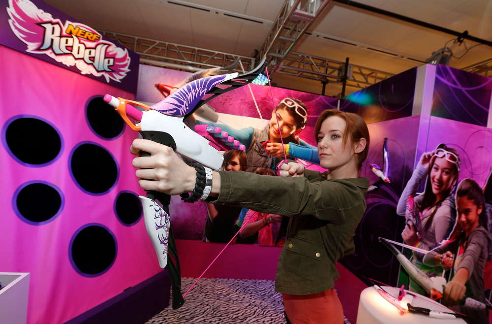 Description of . Demonstrator Kaitlin Large practices with the NERF REBELLE HEARTBREAKER Bow in Hasbroís showroom at the American International Toy Fair, Saturday, Feb. 9, 2013, in New York.  Available at retail Fall 2013, the HEARTBREAKER Bow is part of a collection of bows and blasters inspired by current pop culture trends from the new NERF REBELLE brand, a global lifestyle brand that combines active play with social interaction. (Photo by Jason DeCrow/Invision for Hasbro/AP Images)