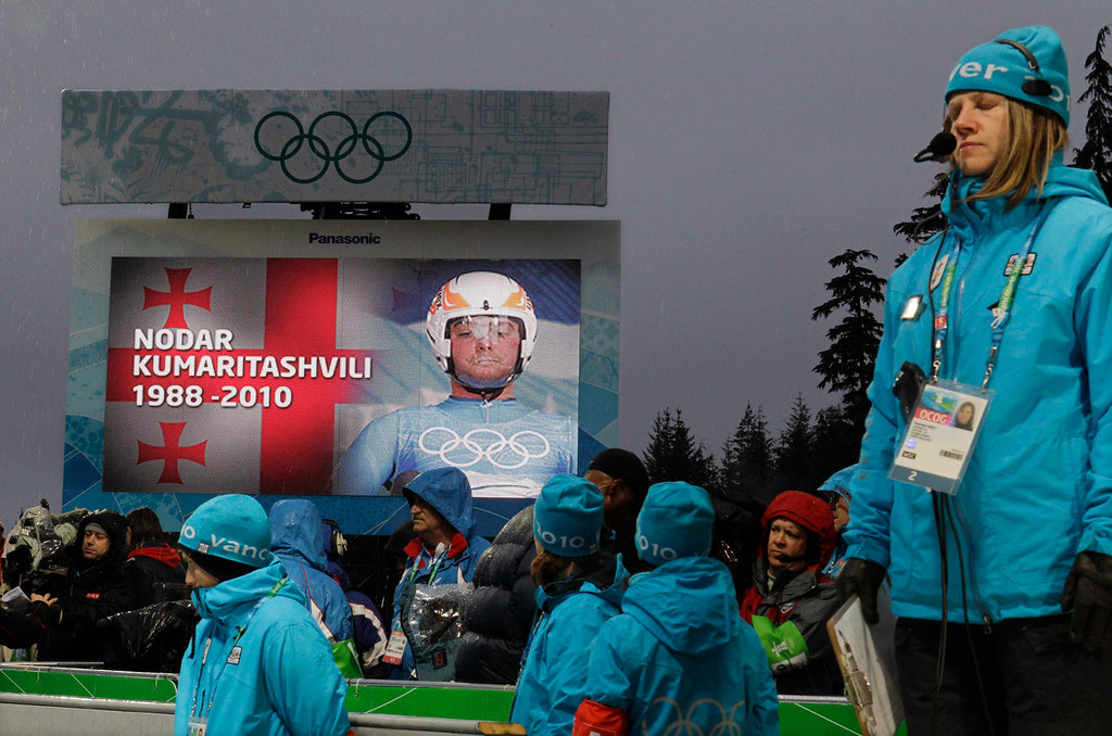 . Track staff observe a moment of silence in honor of Nodar Kumaritashvili of Georgia who died after a training run on Friday, just before the first men\'s singles luge competition run at the Vancouver 2010 Olympics in Whistler, British Columbia, Saturday, Feb. 13, 2010. (AP Photo/Michael Sohn)