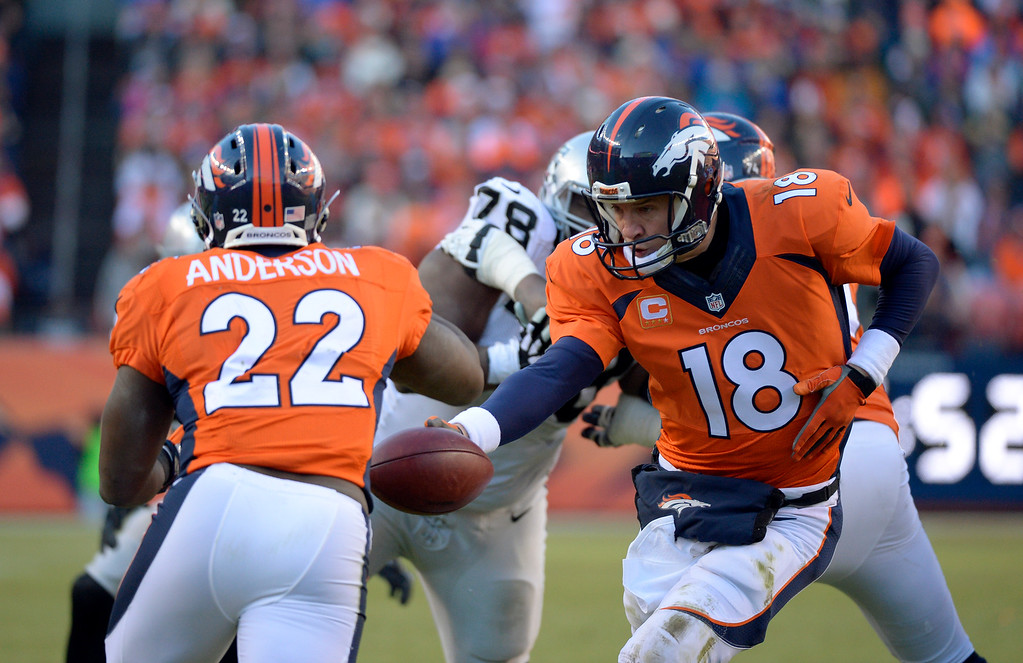 . DENVER, CO - DECEMBER 28: Peyton Manning (18) of the Denver Broncos fakes a hand off to C.J. Anderson (22) of the Denver Broncos during the second quarter.  The Denver Broncos played the Oakland Raiders at Sports Authority Field at Mile High in Denver on December, 28 2014. (Photo by Joe Amon/The Denver Post)