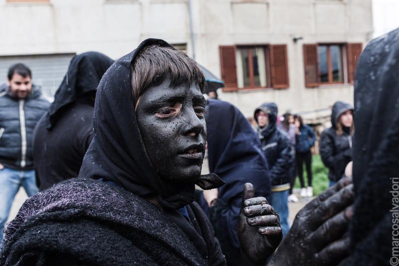 Il volto e le mani colorate di nero con una pasta di sughero bruciato e acqua