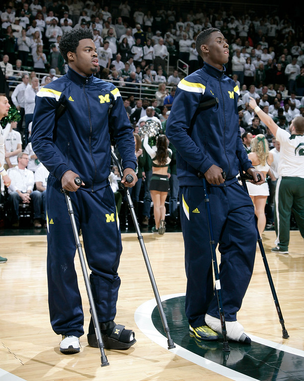 . Injured Michigan players Derrick Walton Jr., left, and Caris LeVert watch warmups while standing on crutches before an NCAA college basketball game against Michigan State, Sunday, Feb. 1, 2015, in East Lansing, Mich. Michigan State won 76-66 in overtime. (AP Photo/Al Goldis)