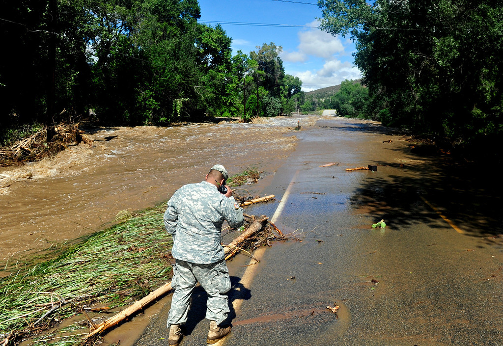 . Colo. National Guard Spec. Jose Alvarez inspects flood damage along Colo. Highway 36 north of Lyons Friday, Sept. 13, 2013. (Greg Lindstrom/Times-Call)