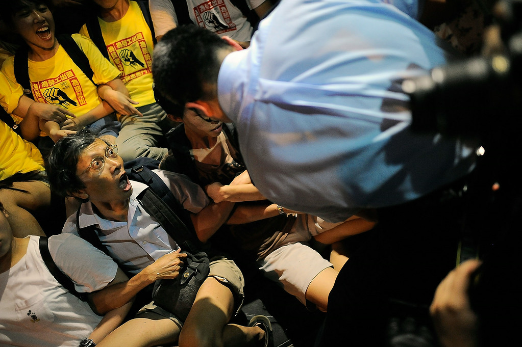 . A protester yells at a police officer as the officer is about to arrest him after the annual pro-democracy protest on July 1, 2014 in Hong Kong. Protesters gathered to occupy a street in Central district. July 1, 2014 marks the 17th anniversary of Hong Kong\'s return to China rule as tens of thousands of Hong Kong residents march on the street to demand for universal suffrage for city\'s next leader.  (Photo by Anthony Kwan/Getty Images)
