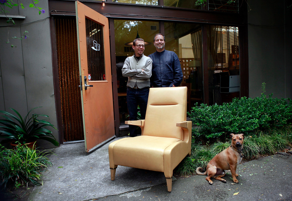 . Ted Boerner, left, and Frank Pontes founded Ted Boerner, Inc., 20 years ago as a San Francisco design studio dedicated to innovative, custom furniture. Now featured in showrooms around the country as well as their own NYC showroom, the pair pose with their signature Lex Club Chair and their dog Nemo at their offices Wednesday, July 11, 2013 in San Francisco, Calif. (Karl Mondon/Bay Area News Group)